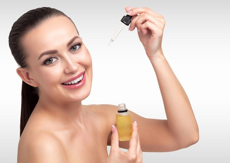 closeup-shot-of-cosmetic-oil-applying-on-young-woman-s-face-with