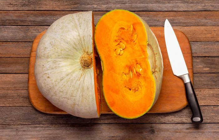 cut-with-a-knife-sweet-ripe-pumpkin-on-a-cutting-board-top-view