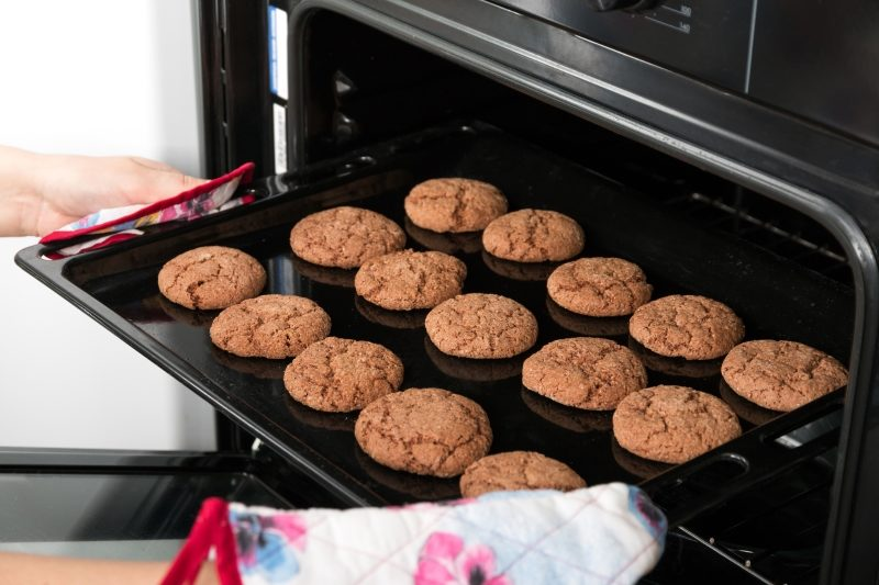 woman-getting-roasting-pan-with-oat-cookies-out-of-oven-2