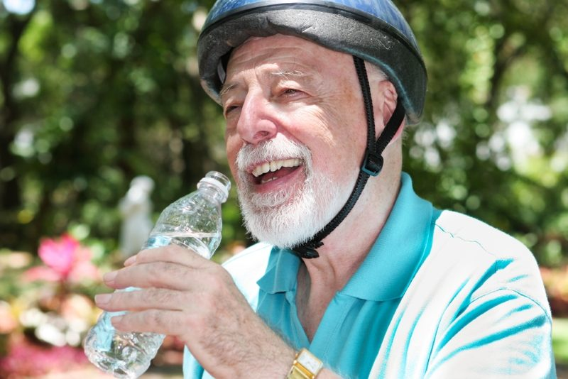 active-senior-man-wearing-a-bicycle-helmet-stops-to-drink-bottled-water-2